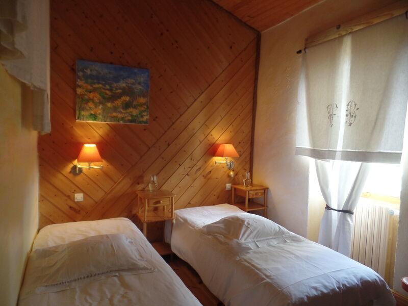 Troisème vue de la chambre Aurore, avec deux lits simples, lampes et mur en lambris