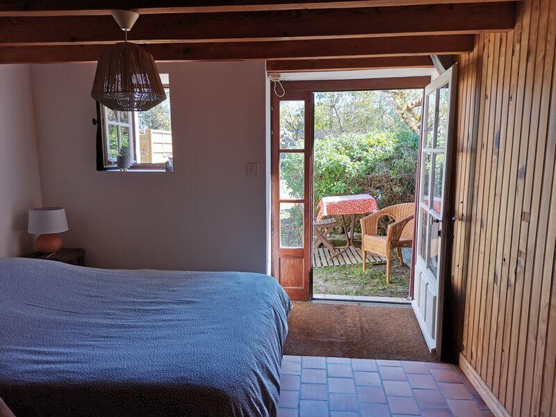 Chambre 1 en rez-de-chaussée, avec lit double et table/lampe de chevet. Carrelage au sol, mur en lambris. Porte fenêtre donnant sur lextérieur, avec petit salon de jardin.