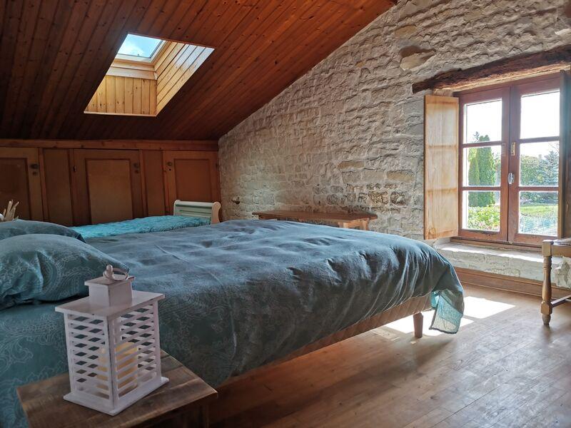 Chambre deux à létage, avec lit double et lit simple. Fenêtre de toit et fenêtre classique, murs en pierre et parquet.
