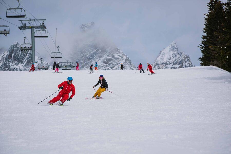 Skieuse adulte avec un moniteur sur le domaine skiable