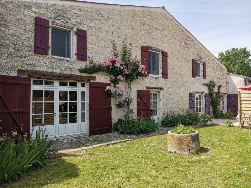Façade en pierre de la maison, plantes fleuries grimpant au mur, volets marrons et verdure.