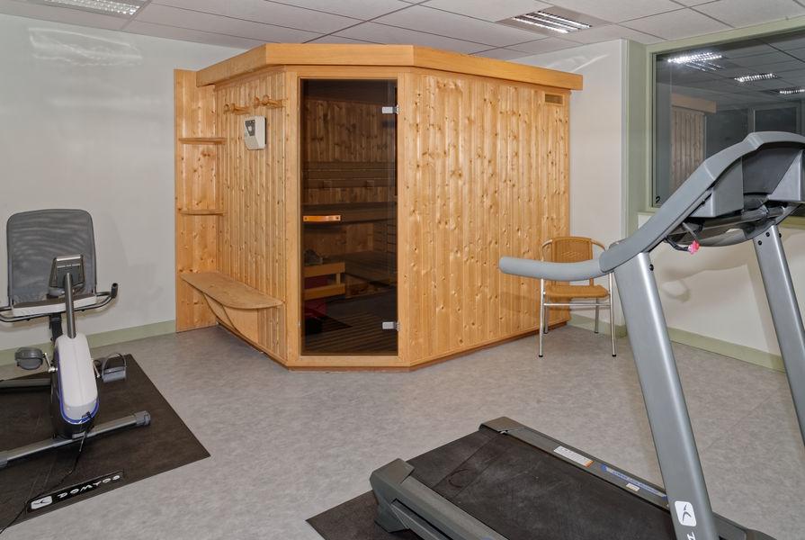 Espace bien-être avec sauna et appareil fitness