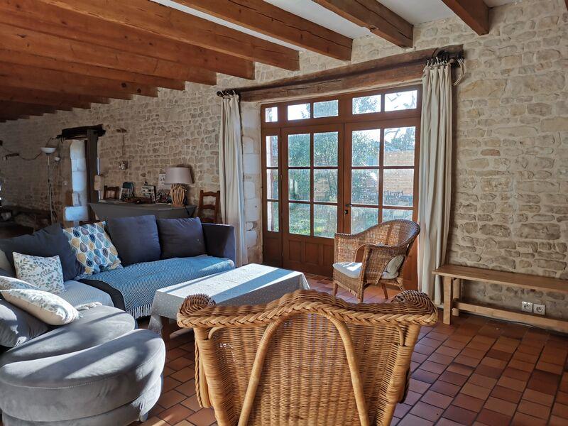 Salon ouvert sur jardin, avec grand canapé dangle gris, deux fauteuils en rotin. Charpente visible, murs en pierre et grande porte-fenêtre.