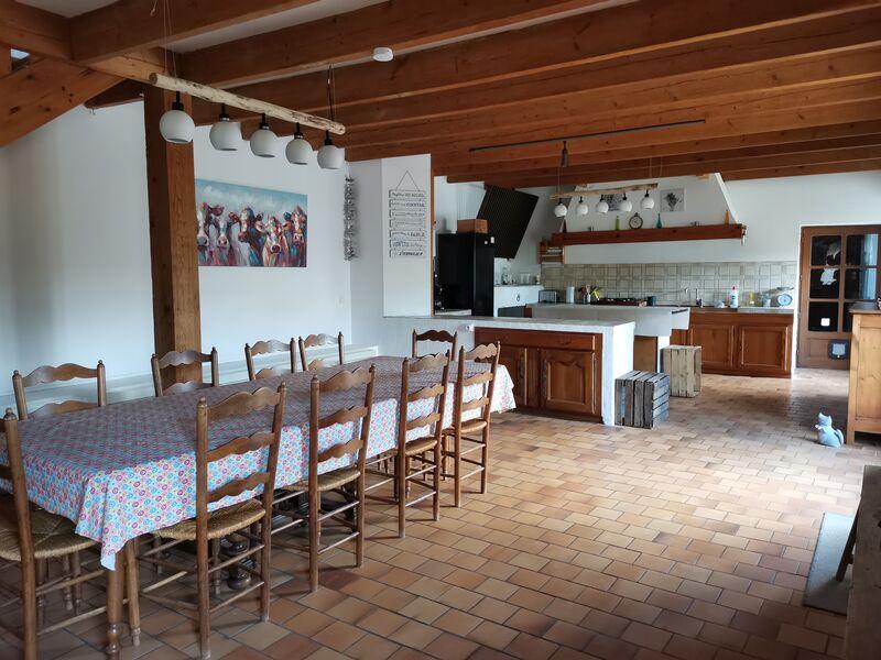 Cuisine ouverte sur espace repas, avec un grande table et 10 chaises, au fond la cuisine. Murs blancs, poutres apparentes au plafond, carrelage marron clair.