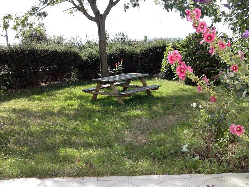 table de pique-nique dans le jardin entouré de buisson et de roses trémières
