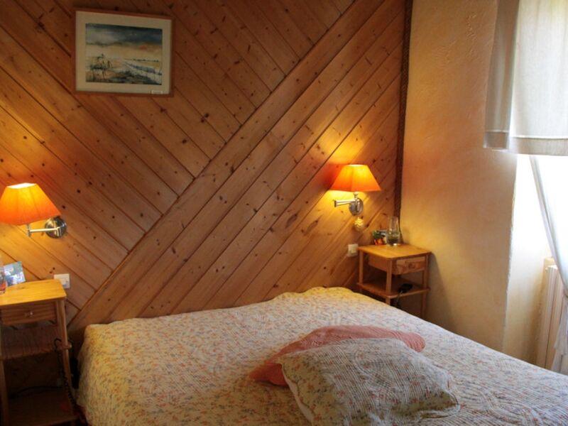 Chambre avec lit double, tables et lampes de chevet, lambris au mur