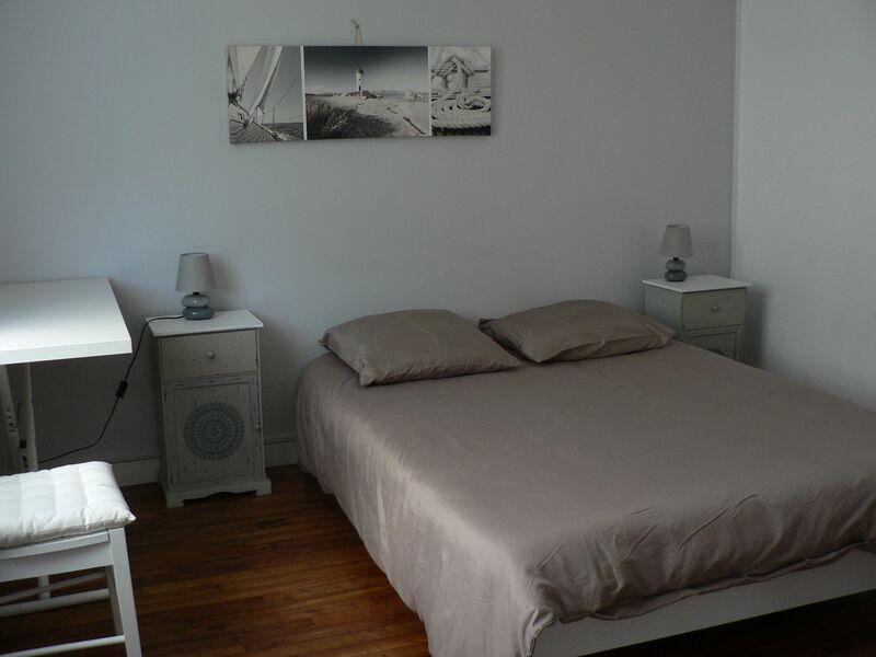 Chambre avec lit double, tables et lampes de chevet, petit bureau et chaise