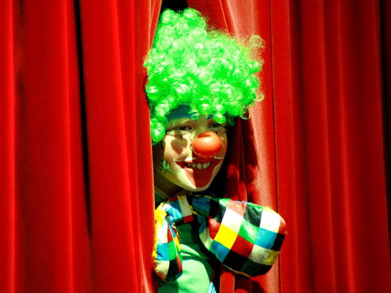 Un clown qui ouvre un rideau rouge